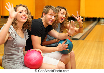 Young man and two happy beautiful girls sit, hold balls and greet someone in bowling club; focus on man