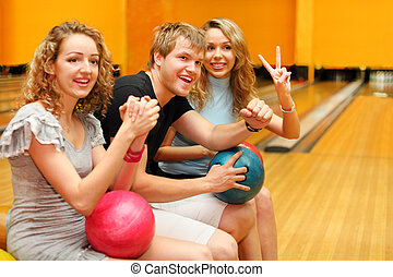 Young man and two happy beautiful girls sit, hold balls and congratulate someone in bowling club; focus on man