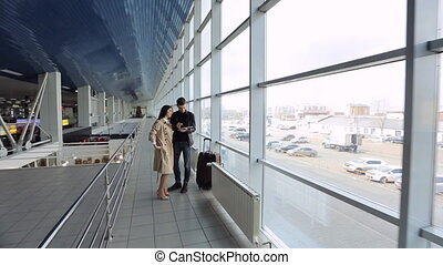 Young man and woman are standing in airport hall talking.