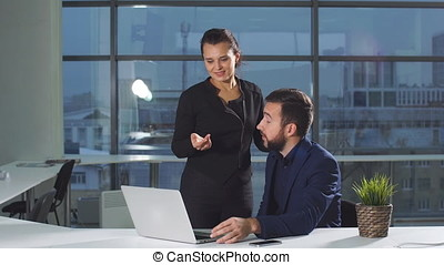 Young man and woman are working on a computer while discussing a project.