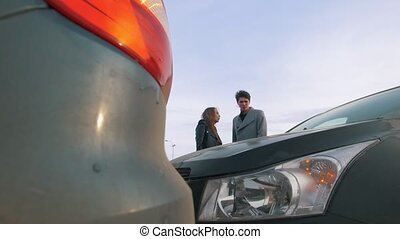 Young man and woman argue a car accident, telephoto shot