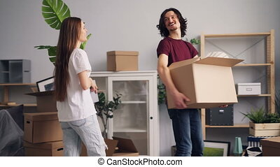 Young man and woman bringing things in boxes to new apartment and kissing