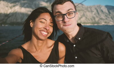 Young man and woman cheerfully doing selfie on ship in open air.