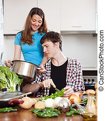 Young man and woman cooking in kitchen