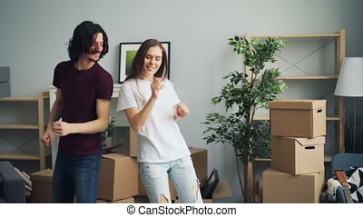 Young man and woman happy couple are dancing, smiling and having fun at home celebrating relocation to new apartment. Carton boxes are visible in background.
