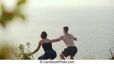 Young man and woman doing morning warm-up on rocky cliff by the river