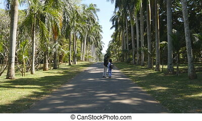 Young Man and woman going along exotic parkland lane, viewing at palm tree and doing selfie photo. Indian couple holding hands of each other and walking in the tropical park. Summer vacation concept