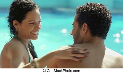 Honeymoon, happy young newlyweds smiling and relaxing near hotel pool