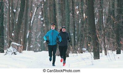 Young man and woman in sport clothes running in winter forest