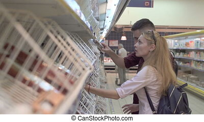 Young man and woman in supermarket choosing goods on the rack, checking them at first