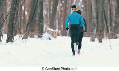 Young man and woman jogging in winter forest