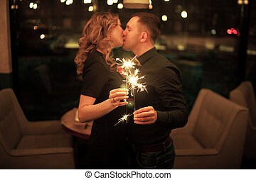 Young man and woman kissing and keeping bengal lights.
