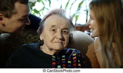 Young man and woman kissing grandmother on cheeks