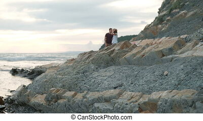 Young man and woman kissing standing on beach on summer evening.