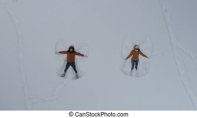 young man and woman making snow angels, aerial
