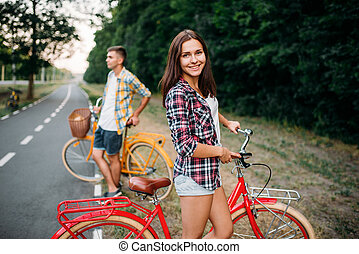 Young man and woman poses with retro bikes