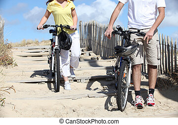 young man and woman riding bikes on the beach