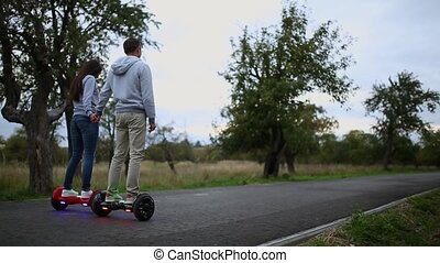 young man and woman riding on the Hoverboard in the park....