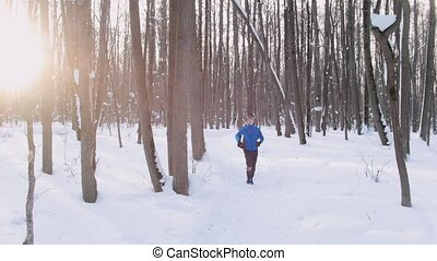 Young man and woman running in winter forest at early morning. Beautiful sunlight. Span camera. Mid shot