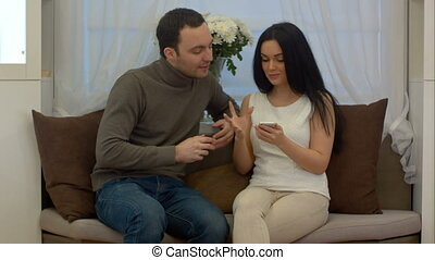 Young man and woman sitting on sofa in living room and discussing something on screen of smart phone