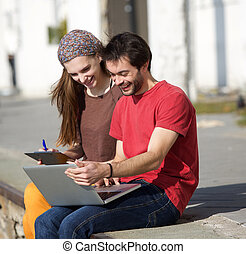 Young man and woman smiling at laptop outdoors