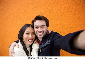 Young man and woman smiling while taking selfie