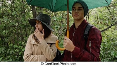 Young man and woman stand under umbrella rain - Young man...