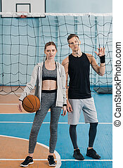 young man and woman standing with ball