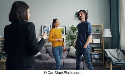 Young man and woman talking to realtor in new house with...