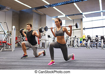 young man and woman training with barbell in gym - sport, ...