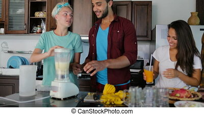 Young Man And Woman Use Blender Prepare Healthy Smoothie Pour It In Glasses People Group Talking Two Couples In Kitchen Cooking Together