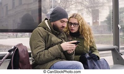 Young man and woman use mobile phone while waiting at a bus stop