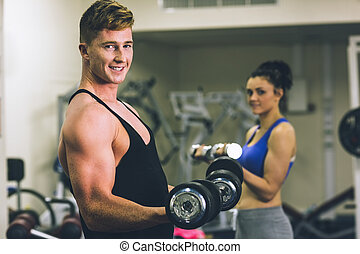Young man and woman using dumbbells in gym