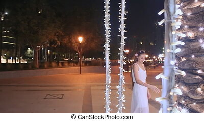 Young man and woman walking among glowing palms trees at night in the city. Girl with love looking at the guy.