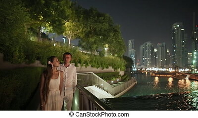 Young man and woman walking in the night Dubai