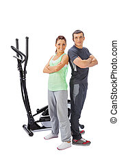 Young man and woman with elliptical cross trainer.