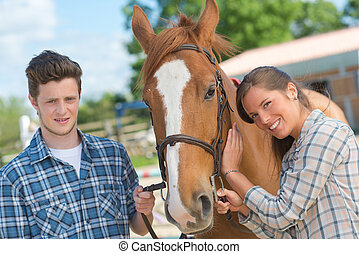 Young man and woman with horse