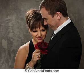 Young  man and woman with red rose in elegant evening dress