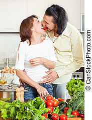 Young man and woman with vegetables in kitchen