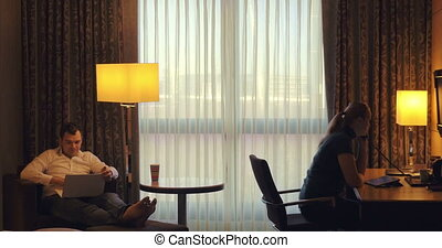 Young man and woman working in hotel room
