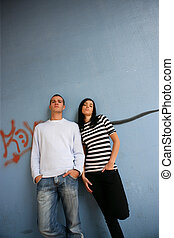 Young man and young woman leaning on a wall