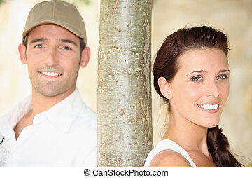 Young man and young woman near a tree