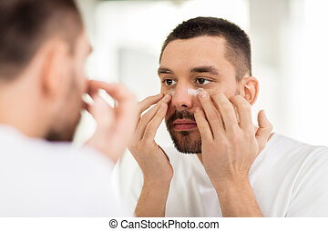 young man applying cream to face at bathroom - grooming,...