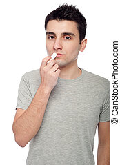 Young man applying lip balm - handsome young man applying ...