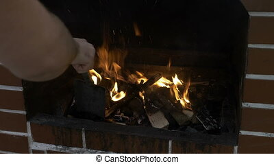 Young man arranging the burning firewood in the fireplace...