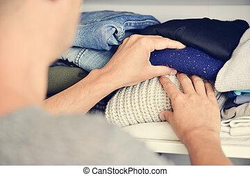 young man arranging the closet