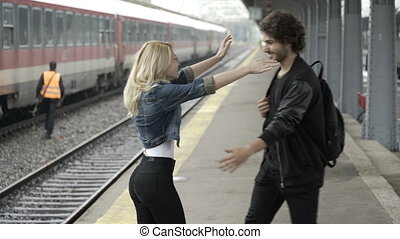 Young man arriving in train station finding his girlfriend eager to meet with him taking selfie with smartphone