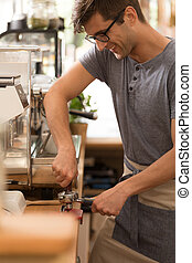 Young man as barista in cafe