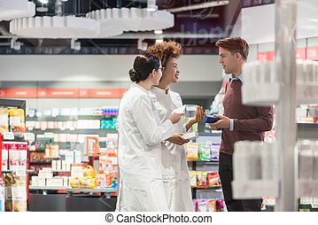 Young man asking for opinion from pharmacists regarding prescrib