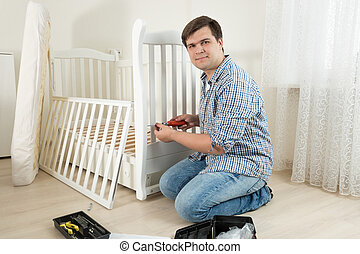 Young man assembling wooden cot in nursery for expectant baby
